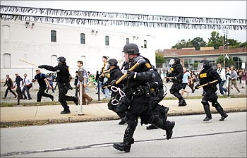 Police officers run to disperse demonstrators during a protest against the G20 Pittsburgh Summit in Pittsburgh.