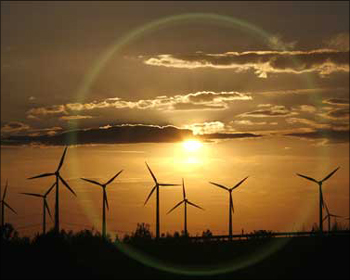 The sun sets behind power-generating windmill turbines.