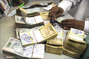 An employee arranges Indian currency notes at a cash counter in a bank.