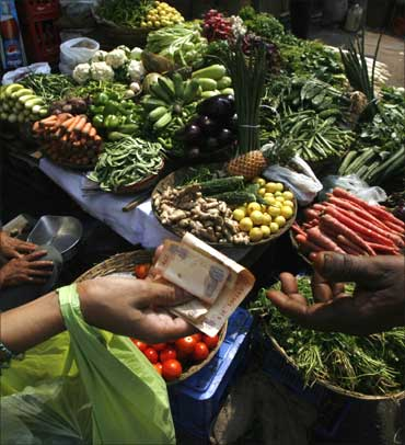 A customer pays money after buying vegetables from a street-side vendor in Mumbai.