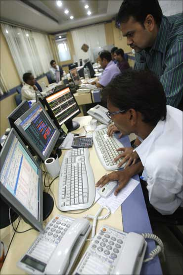 Traders look at their computer screens.