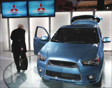 A journalist inspects the 2011 Mitsubishi Outlander sport compact SUV.