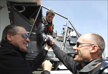Bertrand Piccard (R), pilot and president of Solar Impulse and Andre Borschberg (L), CEO and pilot of the company, congratulate German test pilot Markus Scherdel.