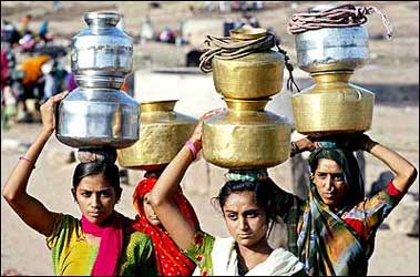 Women carry pitchers filled with drinking water at Siyani village, about 130 km northwest from Ahmedabad.