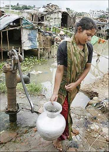 A woman carry drinking water from a village pump.