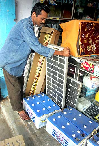 A shopkeeper adjusts a solar panel at his shop in Gosaba.