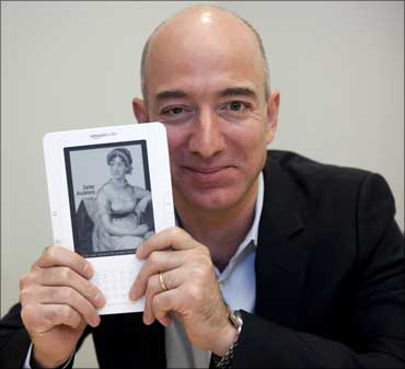 Jeff Bezos, CEO of Amazon.com Inc., shows a Kindle in Cupertino, California.
