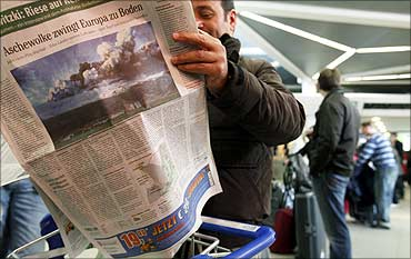 A stranded passenger reads a newspaper as he lines up at a ticket counter at Tegel airport in Berlin