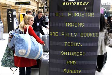Passengers stand next to a Eurostar information sign at Gare du Nord station in Paris.