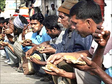 Poor people eat food in front of a temple in New Delhi.
