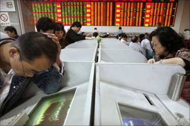 Investors check their stocks value at a stock exchange market in Shanghai.