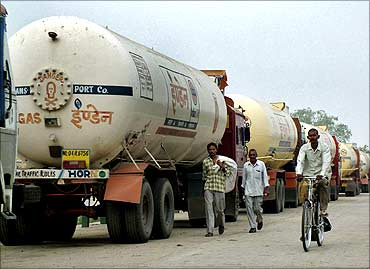 People pass trucks parked near an oil refinery.