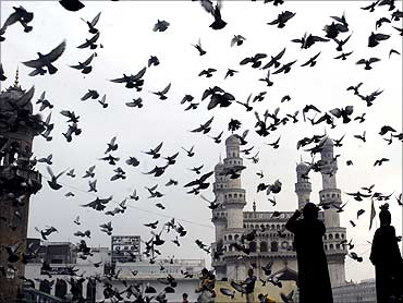 Birds fly off at Charminar in Hyderabad.