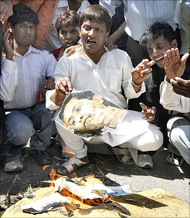 A protester holds a burning photograph of Lalit Modi.