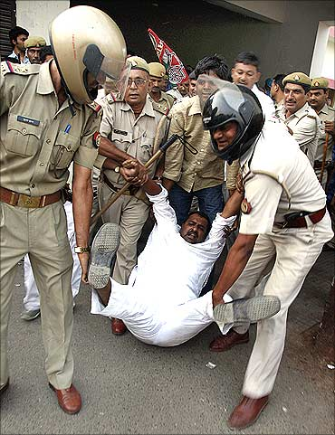 This file photo shows police detaining an activist of Samajwadi Party during a protest against rising inflation in Allahabad.