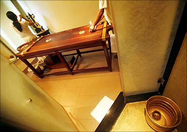 Therapists prepare a traditional Ayurvedic massage room for a customer.