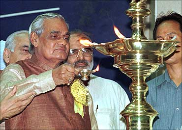 Ex-Indian Prime Minister Atal Behari Vajpayee (L) lights a lamp at an Ayurvedic conference.