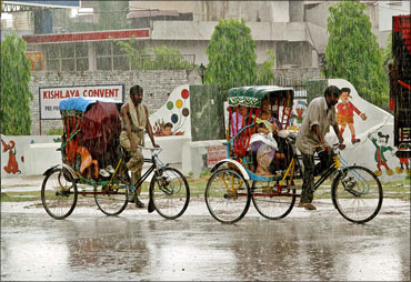 Rickshaw pullers taking passengers in driving rain in Mathura.