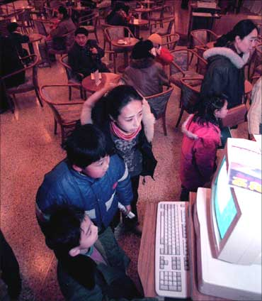 Young Beijing residents accompanied by their parents look over what's on offer at China's first cyber cafe way back in 1996.
