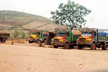 Trucks wait to transport mined ore in Bellary.