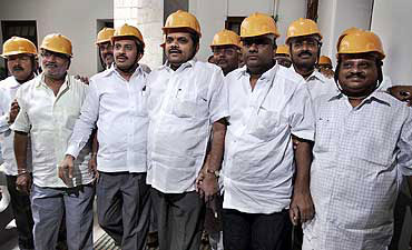 Opposition Karnataka MLAs wear helmets to the assembly to protest against the scam.