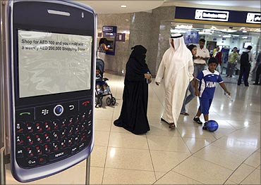 A family walks past a display of a BlackBerry smart phone at a shopping mall.