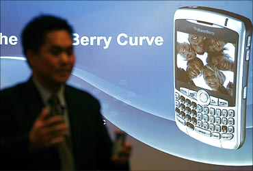 Norm Lee, vice president of Research in Motion, poses with the new Blackberry Curve 8300 phone.