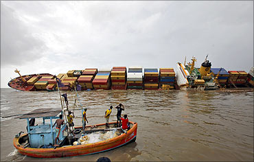Fishermen take pictures of a damaged cargo ship MSC Chitra in the Arabian Sea off the Mumbai coast.