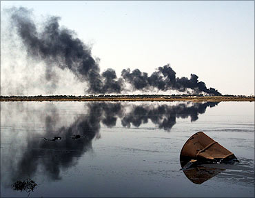 An oil lake lies near a blazing pipeline outside Basra.