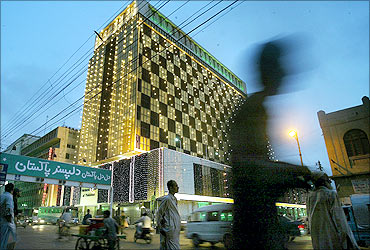 Pakistani pedestrians walk past an illuminated building on the eve of independence day in Karachi.