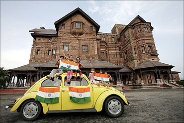 Children hold Indian national flags as they sit on a car in front of Hari Palace during the Independence Day celebrations in Jammu.