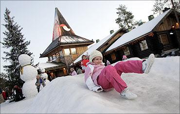 A child slides on the snow in Santa Claus' Village, northern Finland.