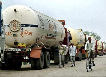 People pass trucks parked near an oil refinery