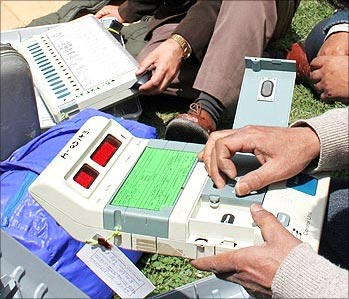 Voting officials checking the EVMs before dispatching them to polling stations
