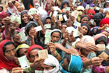 Flood victims show their ID cards to receive food rations at a distribution centre.