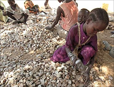 A girl carries her sister as she breaks rocks into smaller pieces to be sold for construction purposes in Juba.