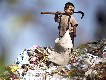 An illegal immigrant boy from Myanmar collects plastic at a rubbish dump site near Mae Sot.