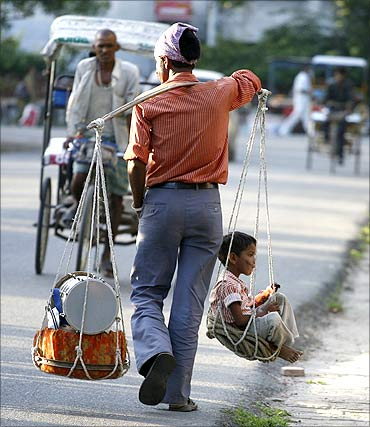 A street performer carries a child in a basket after performing a street show at Noida.