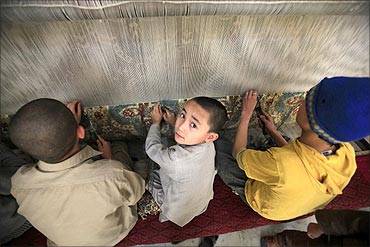 Mohammad Hussain (C), an Afghan boy, weaves carpets with his siblings in Peshawar.