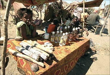 A girl sells beer and food for miners at the Bepeha sapphire mine, Madagascar.