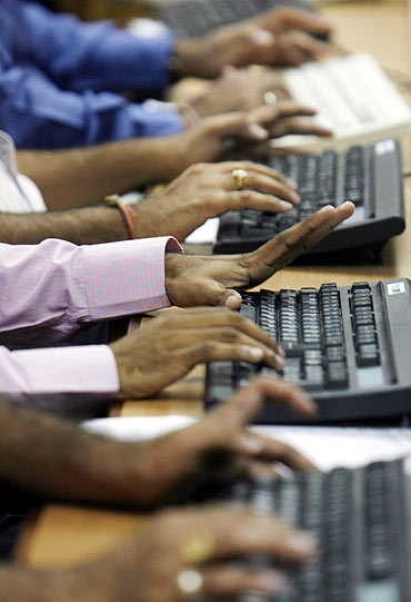 Brokers trade on their computer terminals at a stock brokerage firm in Mumbai.