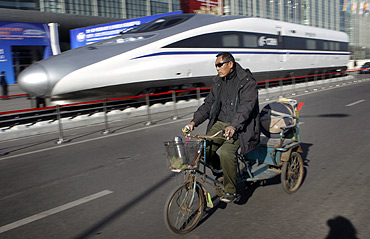 A resident rides a tricycle past the head of a CRH (China Railway High-speed) Harmony bullet train.
