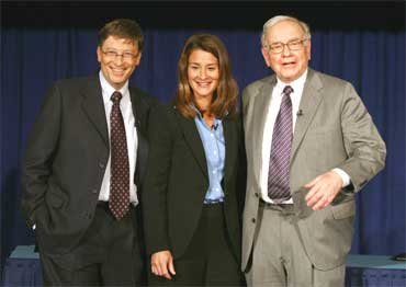 Chairman of Berkshire Hathaway Inc. Warren Buffett (R) poses with Bill and Melinda Gates (C).