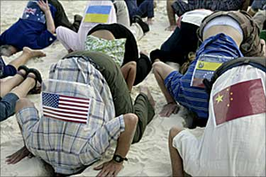 Activists wearing flags representing countries taking part in Cancun climate talks, put their heads in the sand.