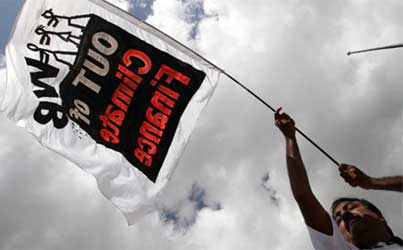 An activist holds a banner during a march in protest against the World Bank's participation in climate finance.