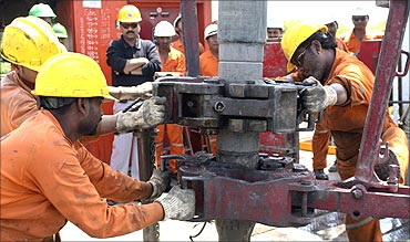 Engineers of Oil and Natural Gas Corp (ONGC) work inside the Kalol oil field.