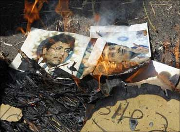People burn photographs of Lalit Modi, chairman of the Indian Premier League.