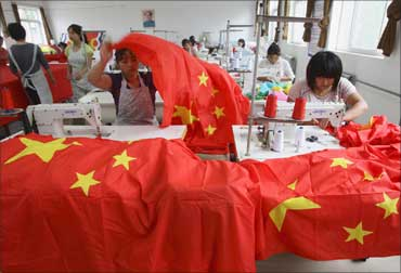 Workers sew Chinese national flags at a factory on the ou
