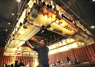 A bartender reaches out for a bottle at a bar in a luxury hotel in Mumbai.