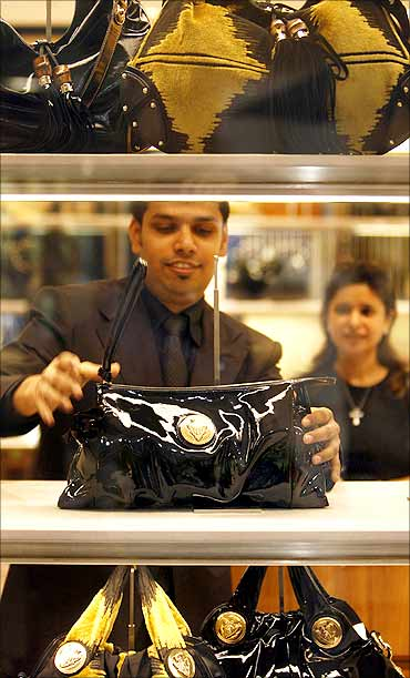 An employee at a Gucci showroom shows products to a customer in Mumbai.